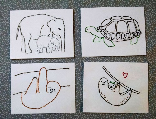 four white notecards embroidered with different animals: top left, an adult and a baby elephant; top right: a tortoise; bottom left, a single sloth hanging from a branch; bottom right, a mother sloth hanging from a branch with her baby