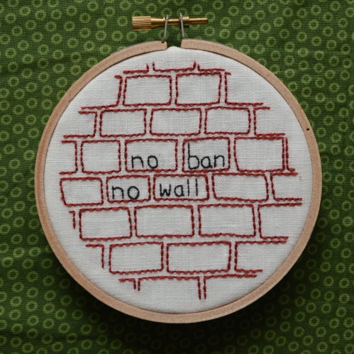 "picture of wooden embroidery hoop with embroidered brick pattern and the words ""no ban no wall"""